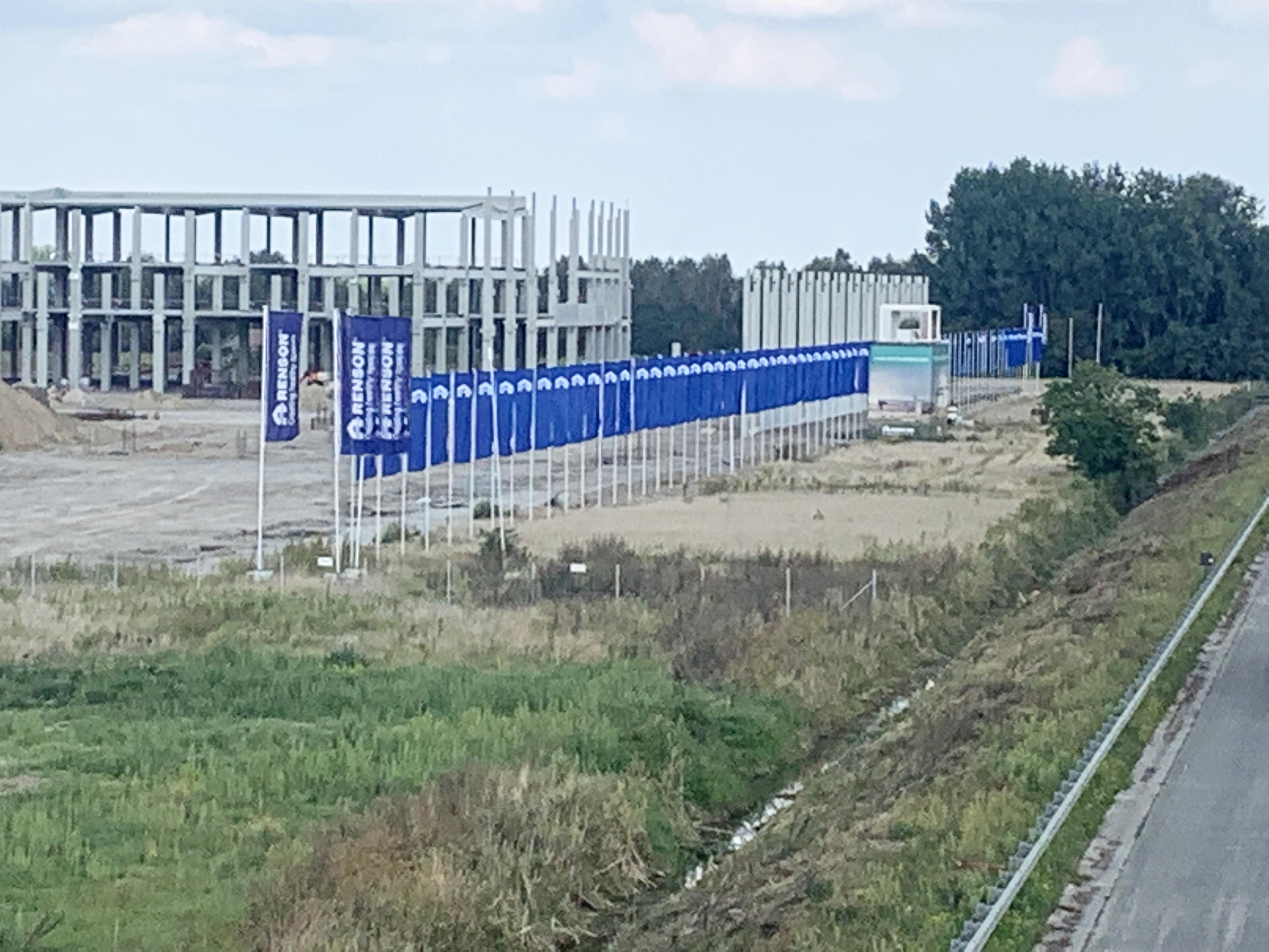 Waelkens vlaggenmasten langs nieuwbouwproject Renson